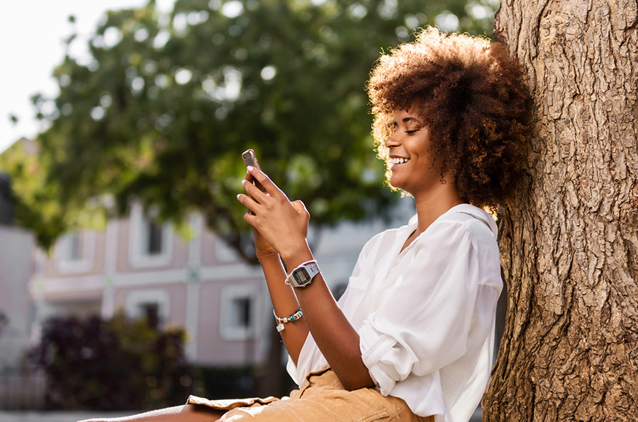 Woman leaning on a tree using phone for online banking