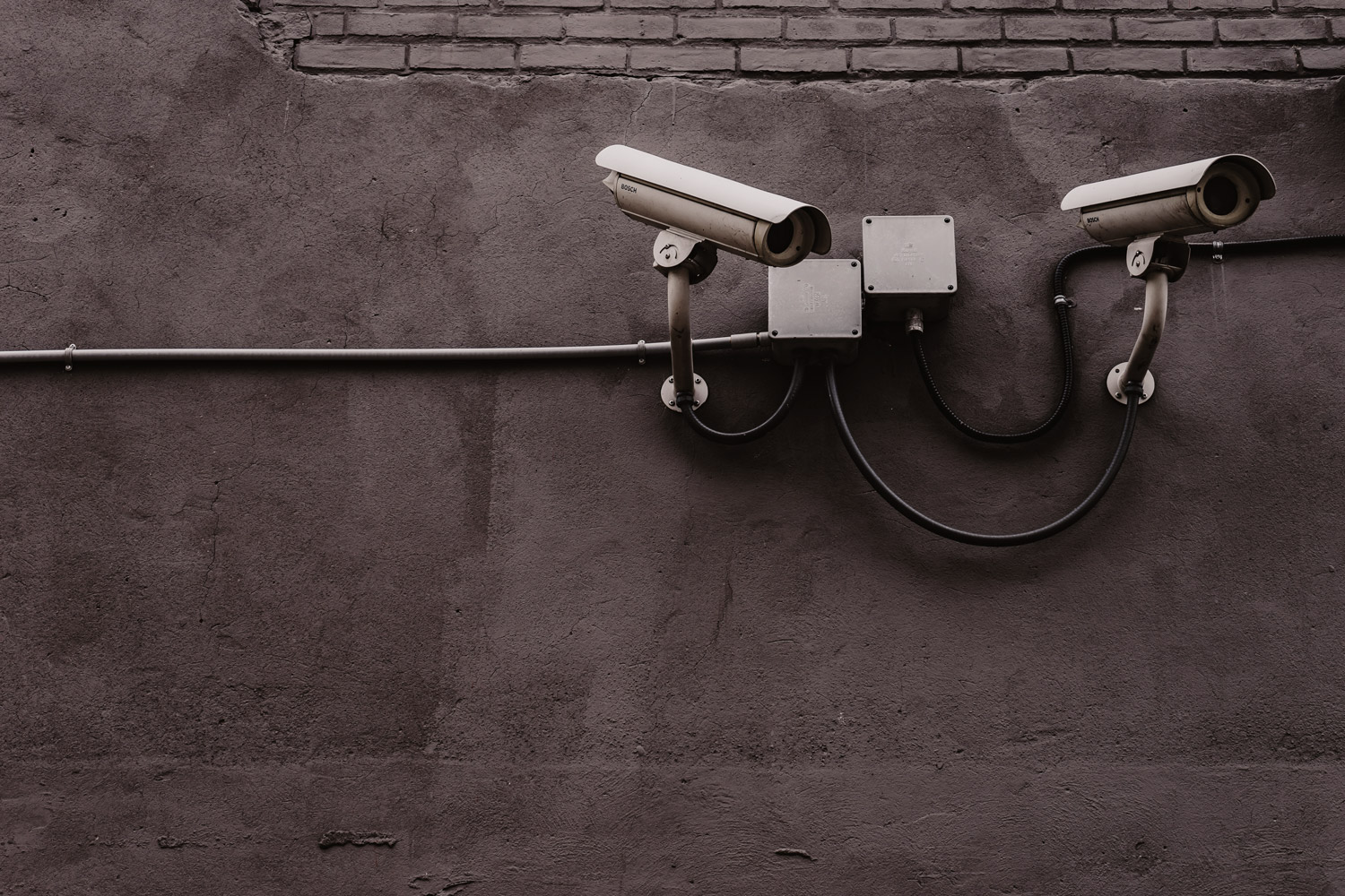 Two bank security cameras on a grey wall